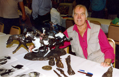 George Montgomery poses beside some of his bronze sculptures at an April 1993 Beverly Garland Hotel autograph show in North Hollywood, CA.