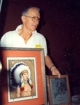 "Keith Larsen holds up a painting of himself as TV's ""Brave Eagle"" and his award at the Memphis, TN, Film Festival in 1992."