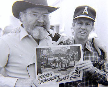 "Gene Evans holds up a lobby card from ""Under Colorado Skies"" ('47 Republic) with Monte Hale, one of Gene's earliest films. It was presented to Gene by stuntman Neil Summers at the Memphis 1984 Film Festival. (Thanx to Grady Franklin.)"
