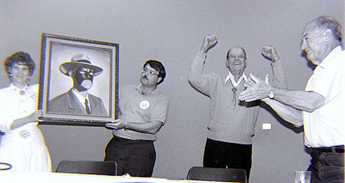Bonnie Boyd and the artist unveil a portrait of Tom Steele as Republic's Masked Marvel at the Knoxville 1990 Western Film Fair. Steele was overjoyed with the painting as director William Witney applauds. (Thanx to Grady Franklin.)