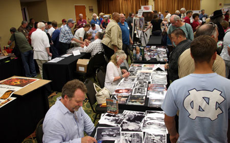 "Darby Hinton and Veronica Cartwright, brother and sister on ""Daniel Boone"", sign autographs for fans in the dealer's room. Don Pedro Colley can be seen standing in the tan jacket."