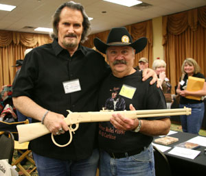 "The Rifleman's real son, Jeff Connors, holds an expertly crafted wooden replica by Stan Wilson (right) of Chuck Connors' rifle from ""The Rifleman""."