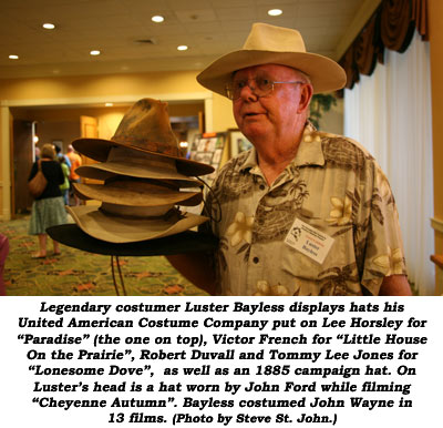 "Legendary costumer Luster Bayless displays hats his United American Costume Company put on Lee Horsley for ""Paradise"" (the one on top), Victor French for ""Little House on the Prairie"", Robert Duvall and Tommy Lee Jones for ""Lonesome Dove"", as well as an 1885 campaign hat. On Luster's head is as hat worn by John Ford while filming ""Cheyenne Autumn"". Bayless costumed John Wayne in 13 films.  (Photo by Steve St. John.)"