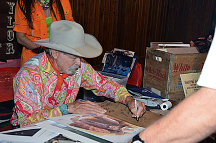 Buck Taylor signs one of his James Arness prints.