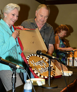 Lee Meriwether, assisted by Boyd Magers accepts a huge Happy Birthday cookie from Trivia Contest winner Don Ellis.