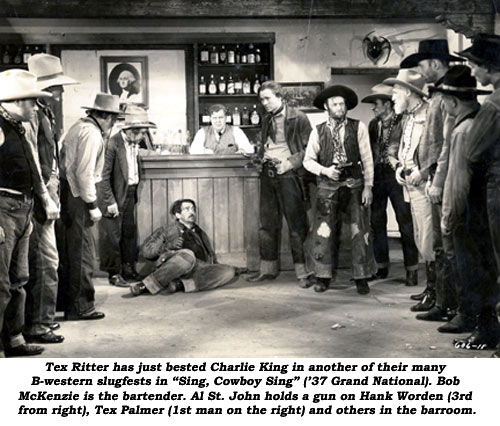 """Tex Ritter has just bested Charlie King in another of their many B-western slugfests in ""Sing, Cowboy, Sing"" ('37 Grand National). Bob McKenzie is the bartender. Al St. John holds a gun on Hank Worden (3rd from right), Tex Palmer (1st man on the right) and others in the barroom."""