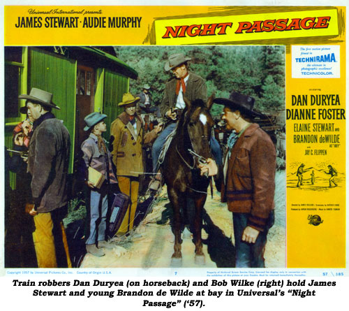 "Train robbers Dan Duryea (on horseback) and Bob Wilke (right) hold James Stewart and young Brandon de Wilde at bay in Universal's ""Night Passage"" ('57)."