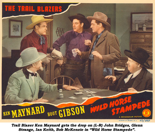 "Trail Blazer Ken Maynard gets the drop on (L-R) John Bridges, Glenn Strange, Ian Keith, Bob McKenzie in ""Wild Horse Stampede."""