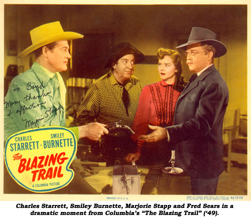"Charles Starrett, Smiley Burnette, Marjorie Stapp and Fred Sears in a dramatic moment from Columbia's ""The Blazing Trail""."