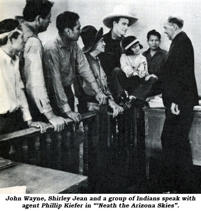 "John Wayne, Shirley Jean and a group of Indians speak with agent Phillip Kiefer in ""'Neath the Arizona Skies""."