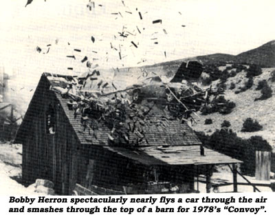 "Bobby Herron spectacularly nearly flys a car through the air and smashes through the top of a barn in 1978's ""Convoy""."