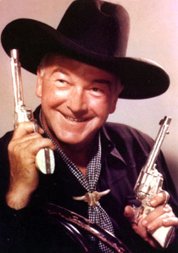 William Boyd as Hopalong Cassidy, guns raised.