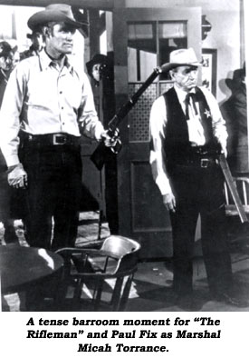"""A tense barroom moment for ""The Rifleman"" and Paul Fix as Marshal Micah Torrance."