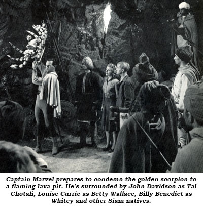 Captain Marvel prepares to condemn the golden scorpion to a flaming lava pit. He's surrounded by John Davidson as Tal Chotali, Louise Currie as Betty Wallace, Billy Benedict as Whitey and other Siam natives.