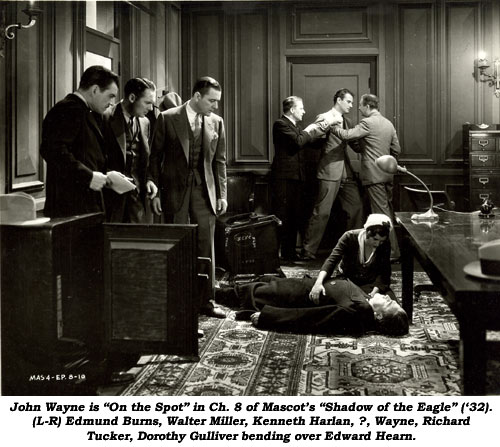 "John Wayne is ""on the spot"" in Ch. 8 of Mascot's ""Shadow of the Eagle"" ('32). (L-R) Edmund Burns, Walter Miller, Kenneth Harlan, ?, Wayne, Richard Tucker, Dorothy Gulliver bending over Edward Hearn."
