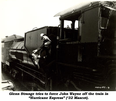 "Glenn Strange tries to force John Wayne off the train in ""Hurricane Express"" ('32 Mascot)."