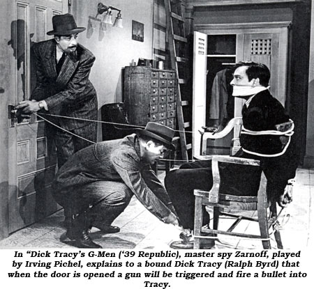 "In ""Dick Tracy's G-Men"" ('39 Republic), master spy Zarnoff, played by Irving Pichel, explains to a bound Dick Tracy (Ralph Byrd) that when the door is opened a gun will be triggered and fire a bullet into Tracy."