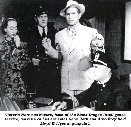 Victoria Horne as Nabura, head of the Black Dragon Intelligence service, makes a call as her aides Gene Roth and Arno Frey hold Lloyd Bridges at gunpoint.