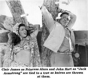 "Clair James as Princess Aluna and John Hart as ""Jack Armstrong"" are tied to a tree as knives are thrown at them."