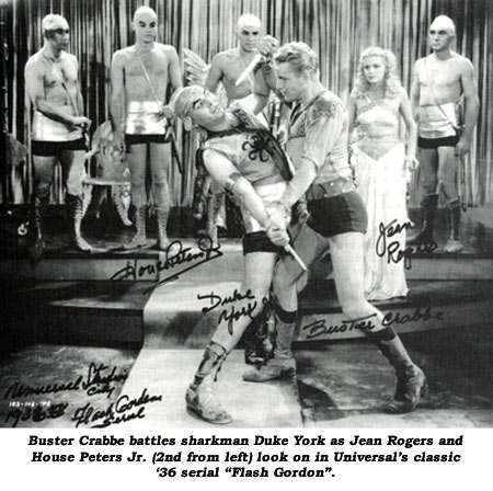 "Buster Crabbe battles sharkman Duke York as Jean Rogers and House Peters Jr. (2nd from left) look on in Universal's classic '36 serial ""Flash Gordon""."