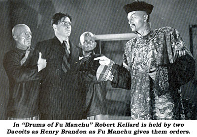 "In ""Drums of Fu Manchu"" Robert Kellard is held by two Dacoits as Henry Brandon as Fu Manchu gives them orders."