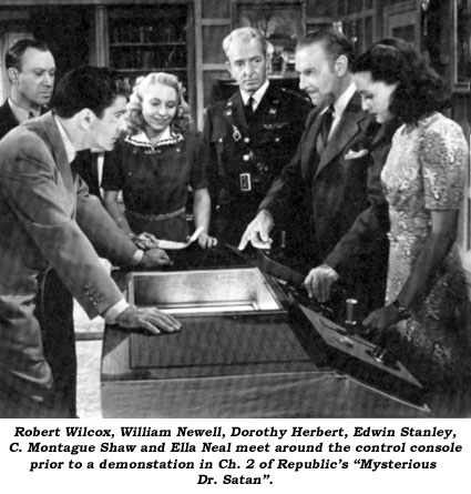"Robert Wilcox, William Newell, Dorothy Herbert, Edwin Stanley, C. Montague Shaw and Ella Neal meet around the control console prior to a demonstration in Ch. 2 of Republic's ""Mysterious Dr. Satan""."