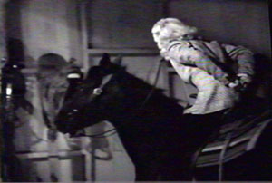 Dorothy, with hands tied behind her back, rides toward window.