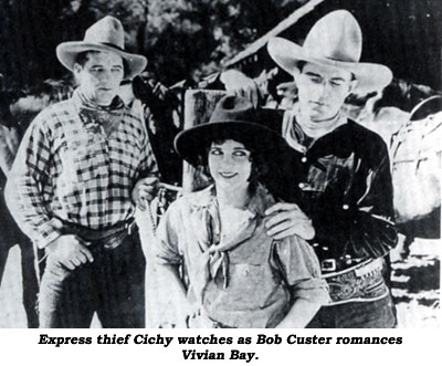"Express thief Cichy watches as Bob Custer romances Vivian Bay in ""Code of the West""."