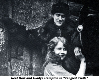 "Neal Hart  and Gladys Hampton in ""Tangled Trails""."