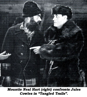 "Mountie Neal Hart (right)A confronts Jules Cowles in ""Tangled Trails""."