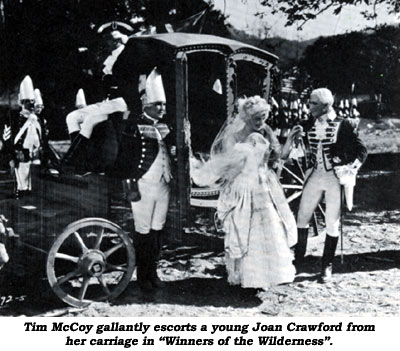 "Tim McCoy gallantly escorts a young Joan Crawford from her carriage in ""Winners of the Wilderness""."