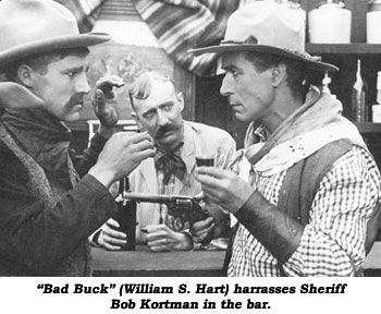 """Bad Buck"" (William S. Hart) harrasses Sheriff Bob Kortman in the bar."