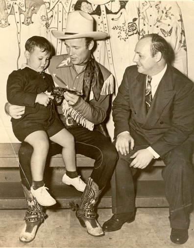 An odd combination! Roy Rogers, King of the Cowboys, with Irving Klaw, King of the Pin-ups--as in Bettie Page--with Klaw's son Arth Klaw at age 4 backstage at the Madison Square Garden Rodeo in 1944.