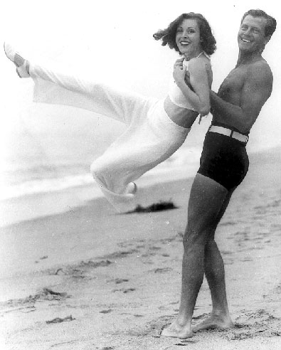 Western star Joel McCrea and his wife Frances Dee cavort on a California beach. Circa 1950's.