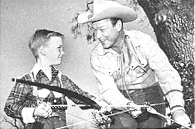 "Roy Rogers teaches his son, eight year old Roy Rogers Jr. (""Dusty""), how to use a bow and arrow for an episode of Roy's TV series, ""Three Masked Men"" which aired on NBC 12/18/55."