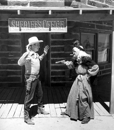 An apparent gag shot as Gene Autry is held up by an old witch on the streets of Pioneertown during the filming of Gene's TV show.
