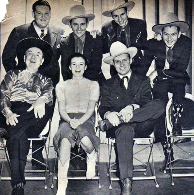 "Gene Autry and his ""Melody Ranch"" radio show gang: (L-R top) announcer Tom Hanlon, The Rough Riders Trio (Jimmy Wakely, Johnny Bond, Dick Reinhart). (L-R seated) Shorty Long as portrayed by Horace Murphy, Mary Lee and Gene Autry."