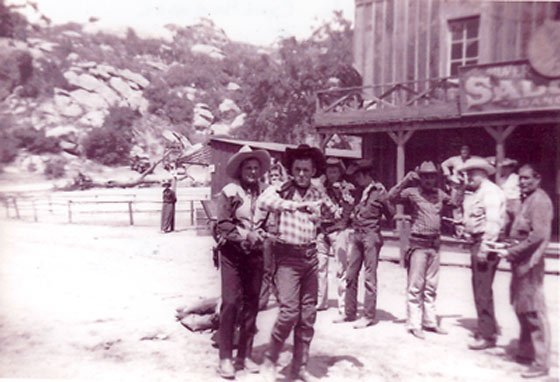 "Ray ""Crash"" Corrigan gets the drop on an outlaw during a live show at Corriganville, circa 1955. Max Terhune (right in white shirt) and Chief Thunder Cloud (far right) hold other outlaws at bay."