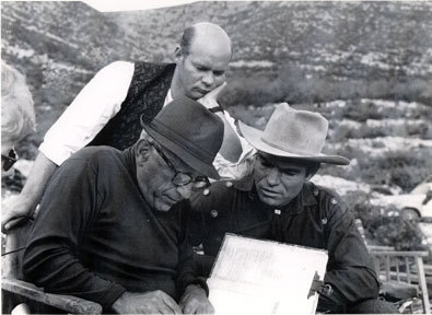 "Director Robert Siodomak and star Kelo Henderson look over the script for the European made ""Pyramid of the Sun God"" ('65) with Kelo and Lex Barker. German actor Ralf Walter peers over their shoulders."