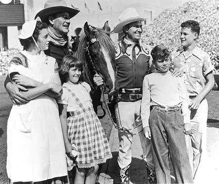 John Wayne and Gene Autry with Wayne's children, Toni, Melinda, Patrick and Michael at the one of the annual Sheriff's Rodeos in L.A. Colisseum. (Photo courtesy Neil Summers.)