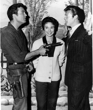 """Whadda mean, you're gonna be a Maverick cousin?"" wonders Ty ""Bronco"" Hardin to Roger Moore. Andrea Martin smiles in the middle."