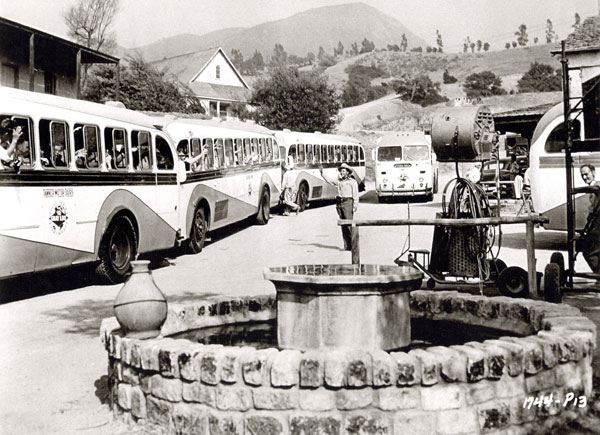 "While filming ""Ride Clear of Diablo"", Audie Murphy waves at the Universal-International tourist buses on the U-I backlot."
