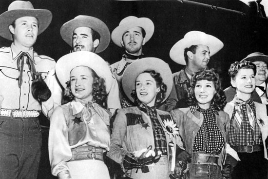 "Promoting the premiere of ""Dodge City"" ('39) in Dodge City, KS are Warner Bros. contractees (back row) Wayne Morris, Gilbert Roland, John Payne, Allan Jones, Frank McHugh. (front row) Priscilla and Rosemary Lane, Jean Parker, Frances Robinson."