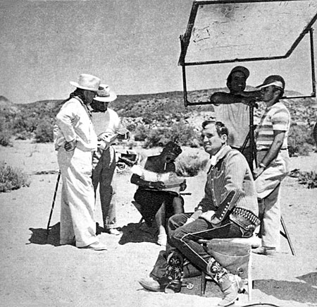 Gene Autry takes a break while technicians make ready for his next scene.