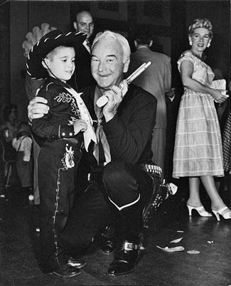 Hopalong Cassidy with a young fan. Hoppy's wife Grace Bradley looks on.