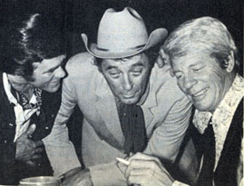 At a 1971 Hollywood party, perhaps a bit tipsy, Christopher George, Robert Mitchum and Peter Graves swap a few lies.