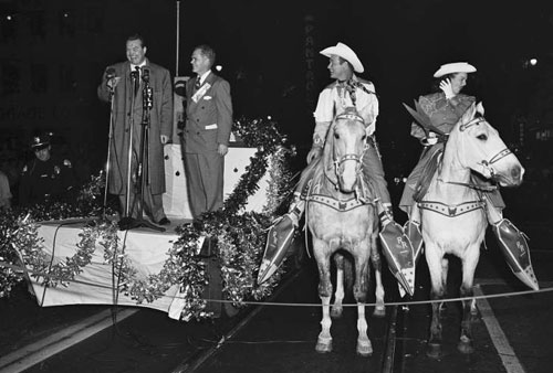 Roy Rogers and Dale Evans on Trigger and Buttermilk await the start of the 1951 Santa Claus Lane Parade in Hollywood while comedian Red Skelton and chairman William Parker kick off the ceremonies.