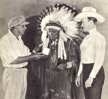 "Tim McCoy looks on while director James Cruze makes a presentation to one of the Indian Chiefs who appeared in ""The Covered Wagon"" ('23)."