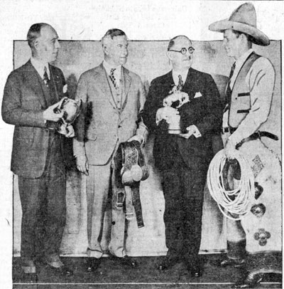 World's Champion Cowboy Yakima Canutt (right) headlined the World's Show Sensations sponsored by the Toledo, OH Shrine club in January 1930. (L-R) Harry Haskell, Ben Groenewold and Mayor William T. Jackson holding some of Yak's trophies.
