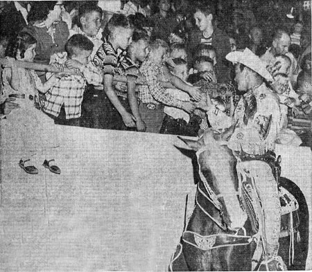 Above three photos taken during Roy Rogers' appearance in early October 1957 for the New Mexico State Fair in Albuquerque. Top photo, Roy signs an autograph for 14 year old Janet Latsha. In the second photo Roy displays one of his guns for two members of a family of ten orphaned earlier in the year, Eddie and Gregory Chavez. In the third photo Roy shakes hands with children at the State Fair Coliseum.